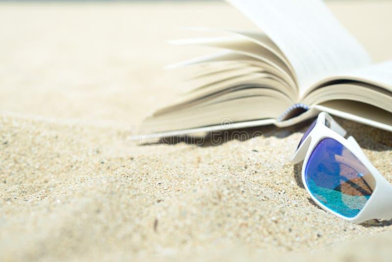 Γυαλιά ηλίου και βιβλίο στην παραλία στοκ φωτογραφίες