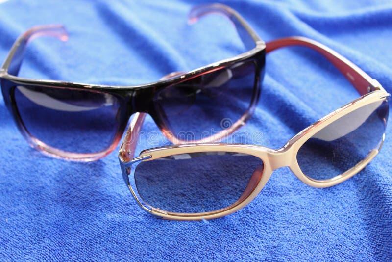 Γυαλιά ηλίου προστασίας γυναικών στο μπλε υπόβαθρο στοκ φωτογραφία με δικαίωμα ελεύθερης χρήσης