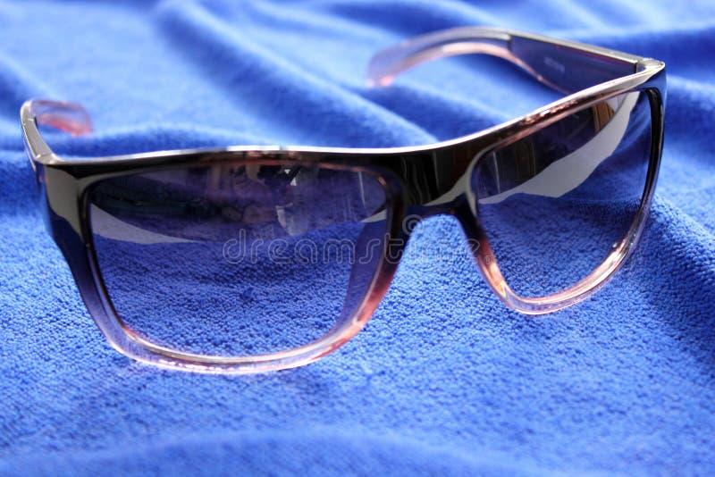 Γυαλιά ηλίου προστασίας γυναικών στο μπλε υπόβαθρο στοκ εικόνες
