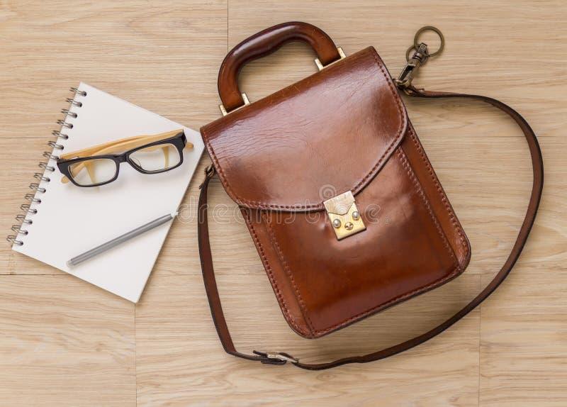 Γυαλιά και μολύβι ματιών σημειωματάριων στο ξύλινο πάτωμα στοκ εικόνα με δικαίωμα ελεύθερης χρήσης