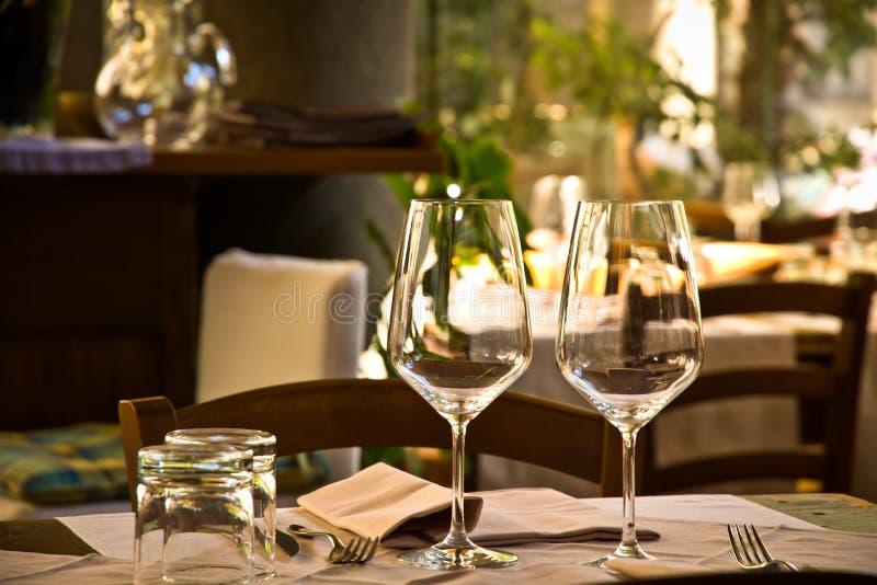 Γυαλιά και πίνακας κρασιού που θέτουν στο εστιατόριο στοκ εικόνες