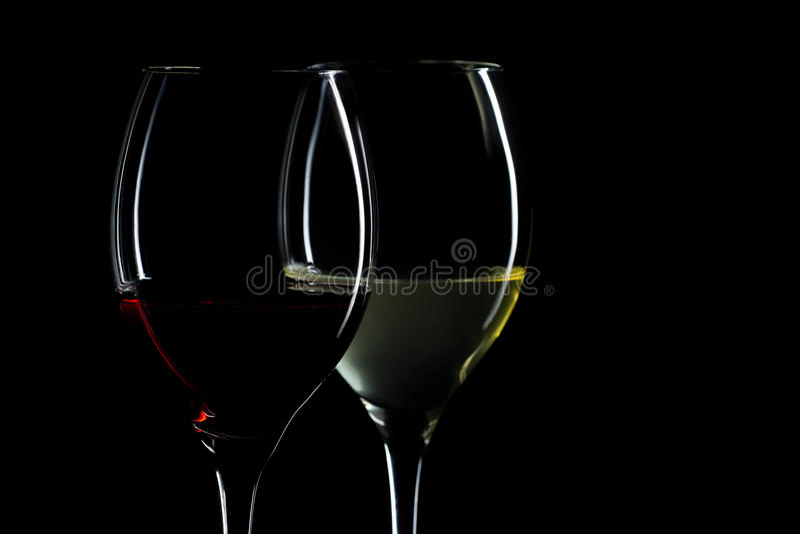 Γυαλιά κρασιού με το κόκκινο και άσπρο κρασί που απομονώνεται στο μαύρο υπόβαθρο στοκ εικόνα