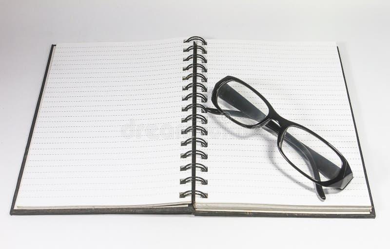 Γυαλιά ματιών με και σημειωματάριο συνδέσμων που απομονώνεται στο άσπρο υπόβαθρο στοκ εικόνα