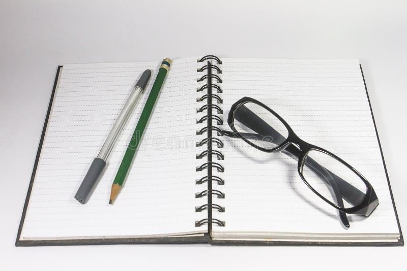 Γυαλιά ματιών με το σημειωματάριο μολυβιών, στυλών και συνδέσμων που απομονώνεται στο άσπρο υπόβαθρο στοκ εικόνα