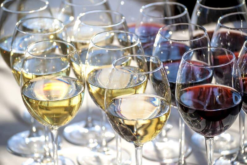 Γυαλιά με την κινηματογράφηση σε πρώτο πλάνο άσπρου και κόκκινου κρασιού στοκ εικόνες