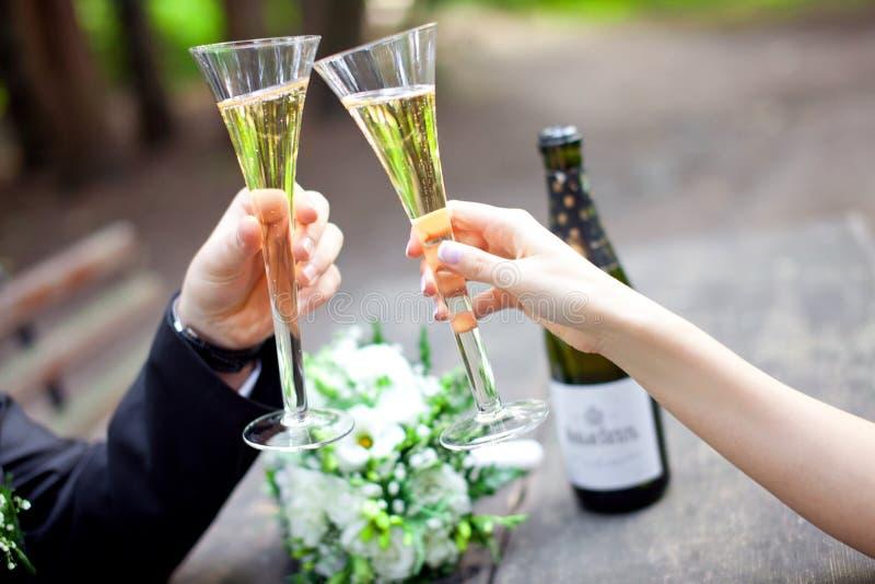 Γυαλιά σαμπάνιας εκμετάλλευσης γαμήλιων ζευγών από κοινού στοκ φωτογραφία