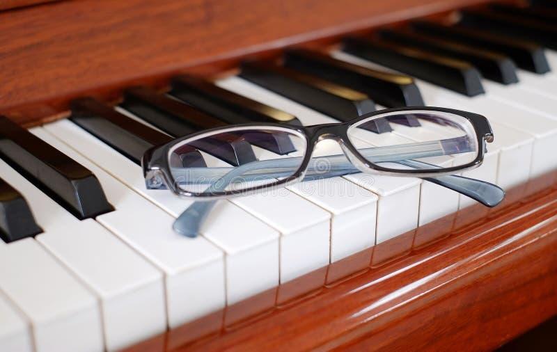 Γυαλιά στο πιάνο στοκ φωτογραφία