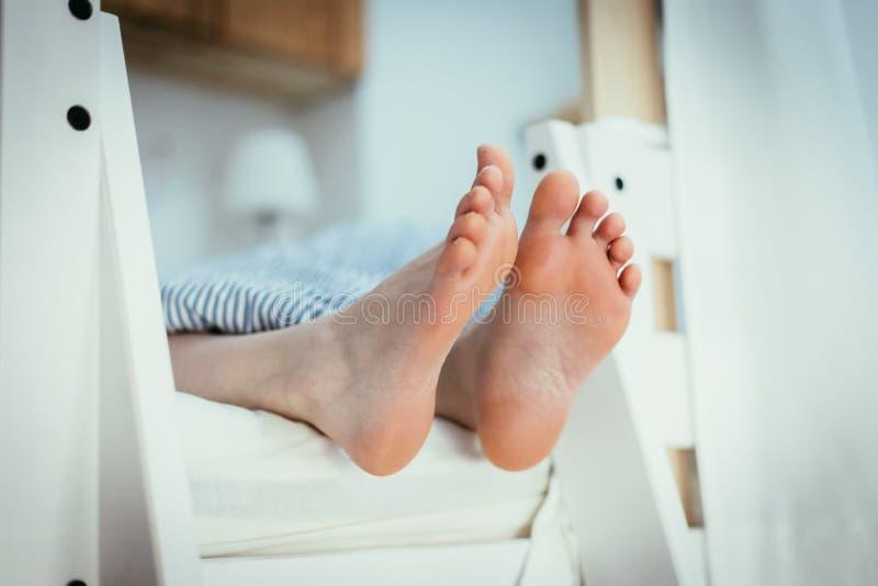 Γυμνά πόδια ενός νέου κοριτσιού στο κρεβάτι, πρωί στοκ εικόνες