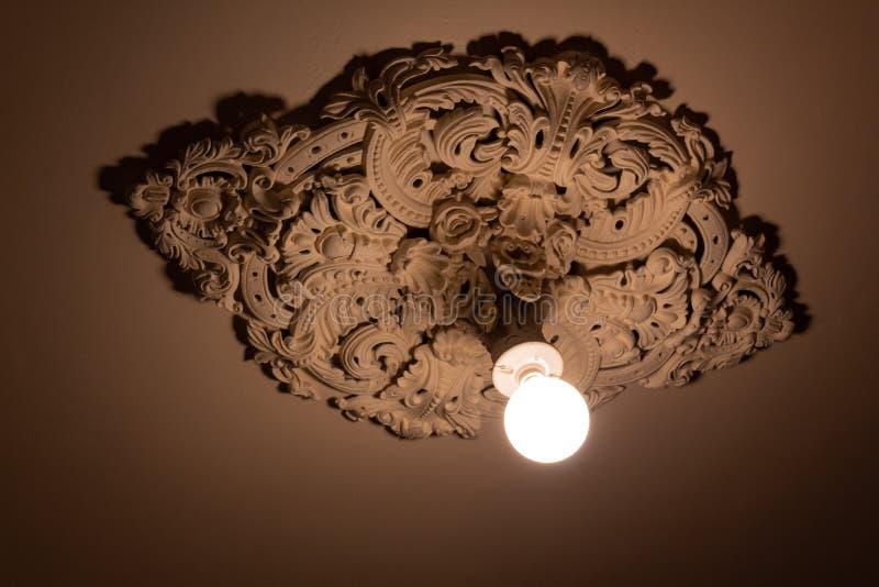 Γυμνή λάμπα φωτός που επεκτείνεται από ένα εξαιρετικά περίκομψο ανώτατο μενταγιόν ασβεστοκονιάματος απορριμμάτων στοκ εικόνες με δικαίωμα ελεύθερης χρήσης