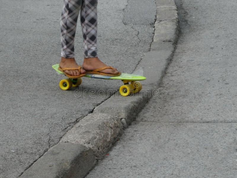 Γυμνός βρώμικος των κοριτσιών πληρώνει στις παντόφλες skateboard στοκ εικόνα
