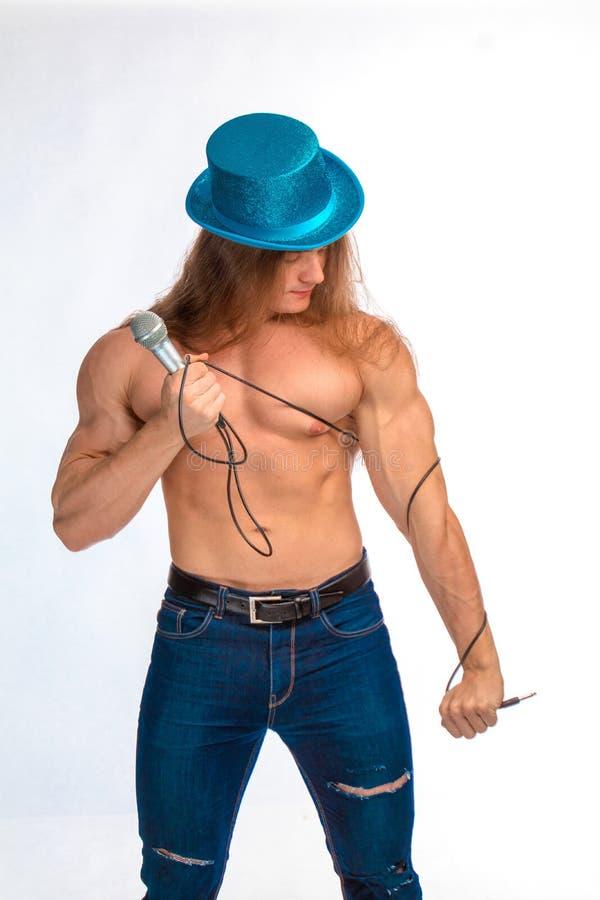 Γυμνόστηθος τραγουδιστών bodybuilder με μακρυμάλλη σε ένα μπλε καπέλο με ένα μικρόφωνο στοκ εικόνες