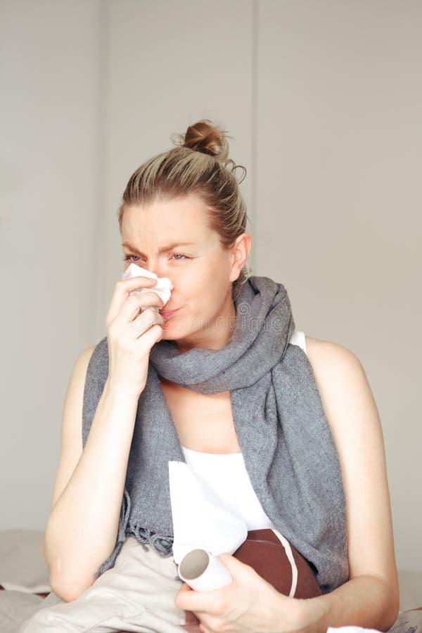 Γυναίκα άρρωστη στο σπορείο που φυσά τη μύτη της στοκ εικόνα με δικαίωμα ελεύθερης χρήσης