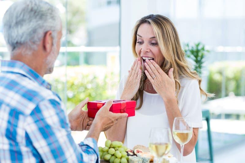 Γυναίκα έκπληκτη ενώ σύζυγος που δίνει το δώρο στοκ φωτογραφία με δικαίωμα ελεύθερης χρήσης