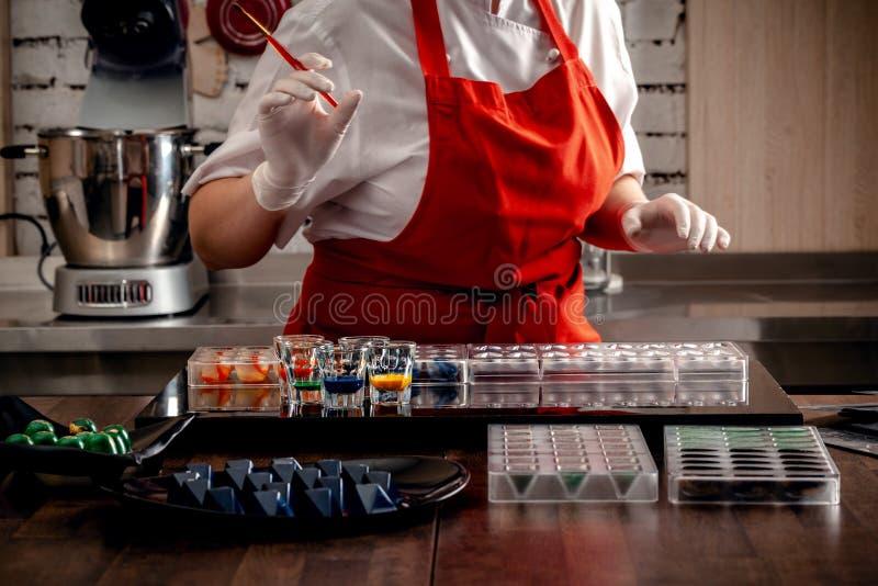 Γυναίκα ένας ζαχαροπλάστης στα κόκκινα ομοιόμορφα και άσπρα γάντια που κάνουν την καραμέλα στις ειδικές μορφές από τη γαλακτοκομι στοκ φωτογραφίες με δικαίωμα ελεύθερης χρήσης