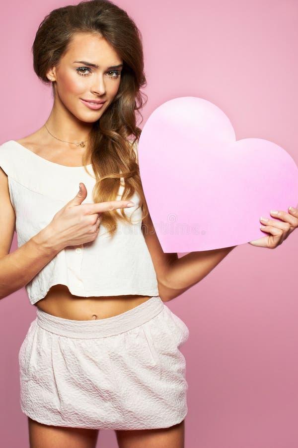 Γυναίκα αγάπης και ημέρας βαλεντίνων που κρατούν το ρόδινο χαμόγελο καρδιών χαριτωμένο και λατρευτός που απομονώνεται στο ρόδινο  στοκ εικόνα