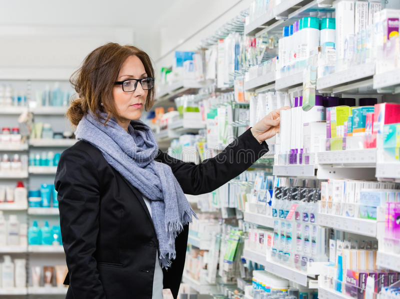 Γυναίκα αγοραστής που επιλέγει το προϊόν στο φαρμακείο στοκ εικόνα