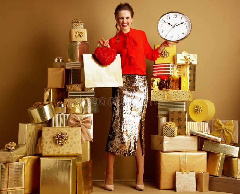 Γυναίκα αγοραστών με την τσάντα αγορών και την κόκκινη καρδιά που παρουσιάζουν ρολόι στοκ εικόνα με δικαίωμα ελεύθερης χρήσης