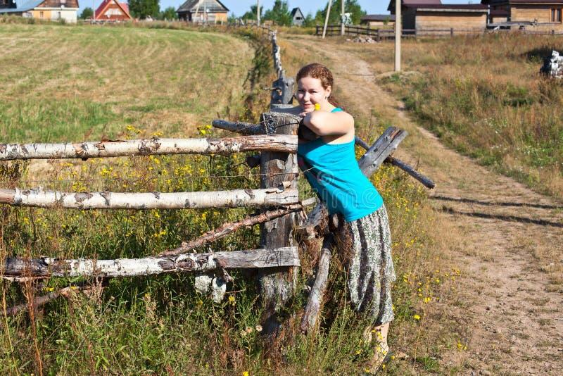 Γυναίκα αγροτών που στέκεται κοντά στον του χωριού φράκτη στοκ εικόνα
