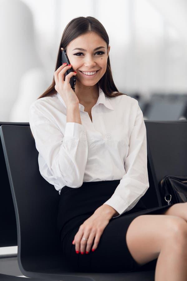 Γυναίκα αερολιμένων στο έξυπνο τηλέφωνο στην πύλη που περιμένει στο τερματικό Έννοια αεροπορικού ταξιδιού με τη νέα περιστασιακή  στοκ εικόνες με δικαίωμα ελεύθερης χρήσης