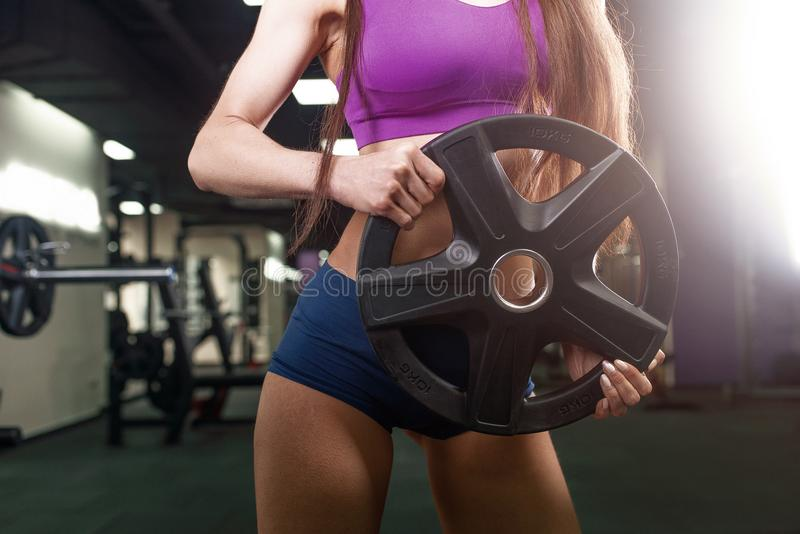 Γυναίκα αθλητών που επιλύει με το barbell Κορίτσι ικανότητας μπικινιών sportswear που κάνει την άσκηση στη γυμναστική στοκ εικόνα
