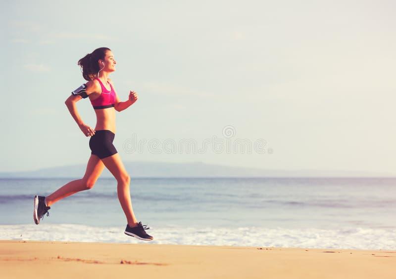 Γυναίκα αθλητικής ικανότητας που τρέχει στην παραλία στο ηλιοβασίλεμα στοκ εικόνες