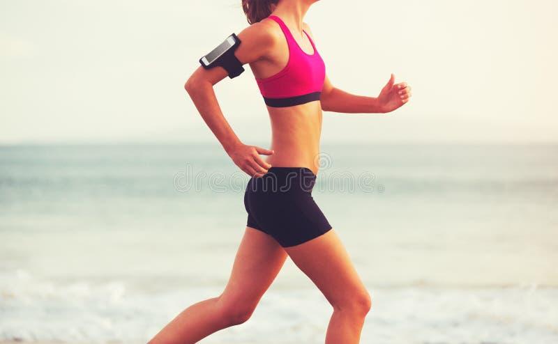 Γυναίκα αθλητικής ικανότητας που τρέχει στην παραλία στο ηλιοβασίλεμα στοκ φωτογραφίες με δικαίωμα ελεύθερης χρήσης