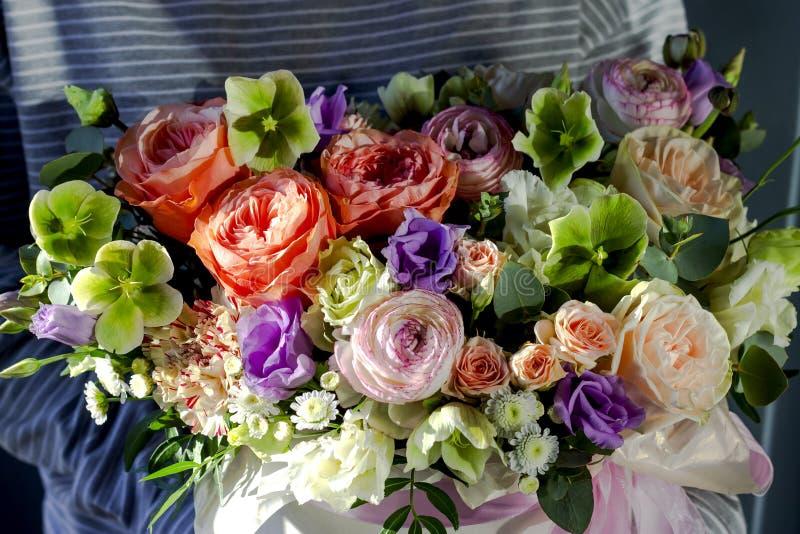 Γυναίκα ανθοκόμων που κρατά μια όμορφη ρύθμιση λουλουδιών σε ένα floral υπόβαθρο ανθοπωλείων στοκ φωτογραφίες
