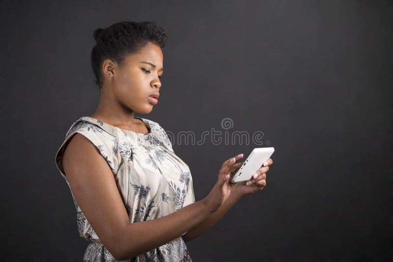 Γυναίκα αφροαμερικάνων με την ταμπλέτα στο υπόβαθρο πινάκων στοκ εικόνες