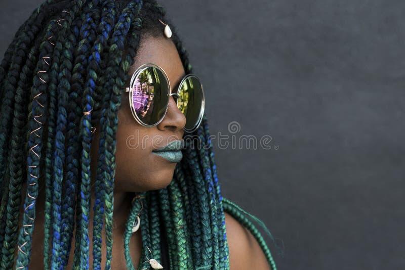 Γυναίκα αφροαμερικάνων με τις όμορφες πράσινες μπλε πλεξούδες κιρκιριών στοκ εικόνα