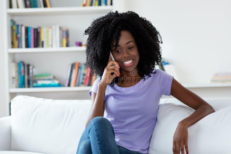 Γυναίκα αφροαμερικάνων που μιλά με άλλο θηλυκό στο τηλέφωνο στοκ φωτογραφία
