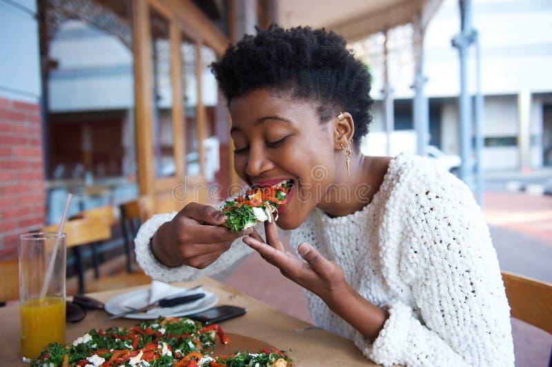 Γυναίκα αφροαμερικάνων που τρώει την πίτσα στο υπαίθριο εστιατόριο στοκ εικόνες