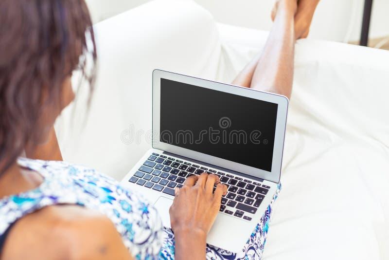 Γυναίκα αφροαμερικάνων που χρησιμοποιεί το lap-top στοκ εικόνα με δικαίωμα ελεύθερης χρήσης