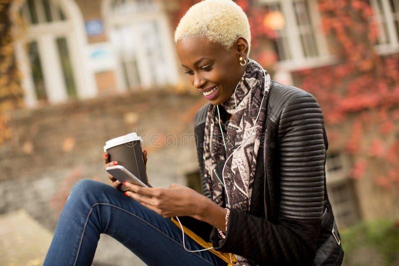 Γυναίκα αφροαμερικάνων Atrractive στο πάρκο φθινοπώρου στοκ εικόνες