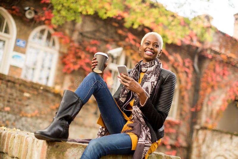 Γυναίκα αφροαμερικάνων Atrractive στο πάρκο φθινοπώρου στοκ φωτογραφία