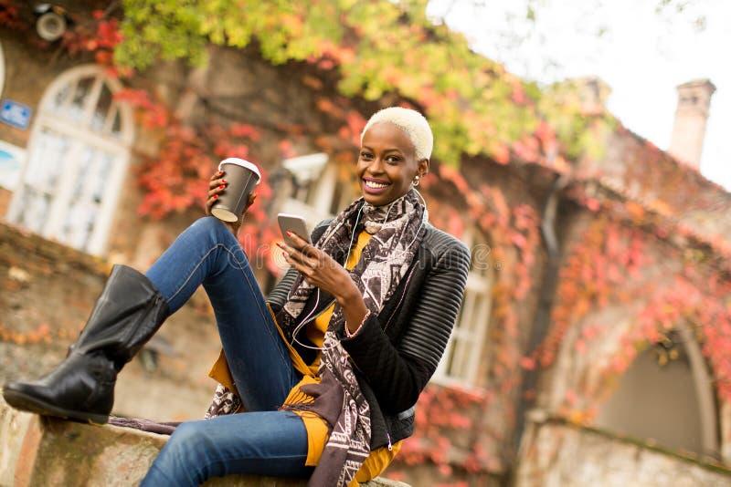 Γυναίκα αφροαμερικάνων Atrractive στο πάρκο φθινοπώρου στοκ εικόνα