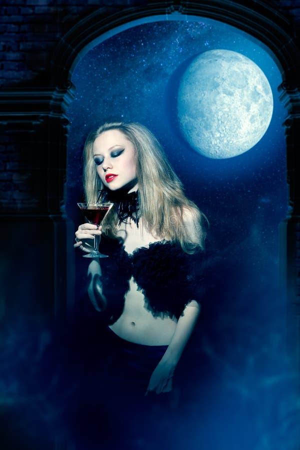 Γυναίκα βαμπίρ με το ποτήρι του κρασιού στοκ εικόνα με δικαίωμα ελεύθερης χρήσης