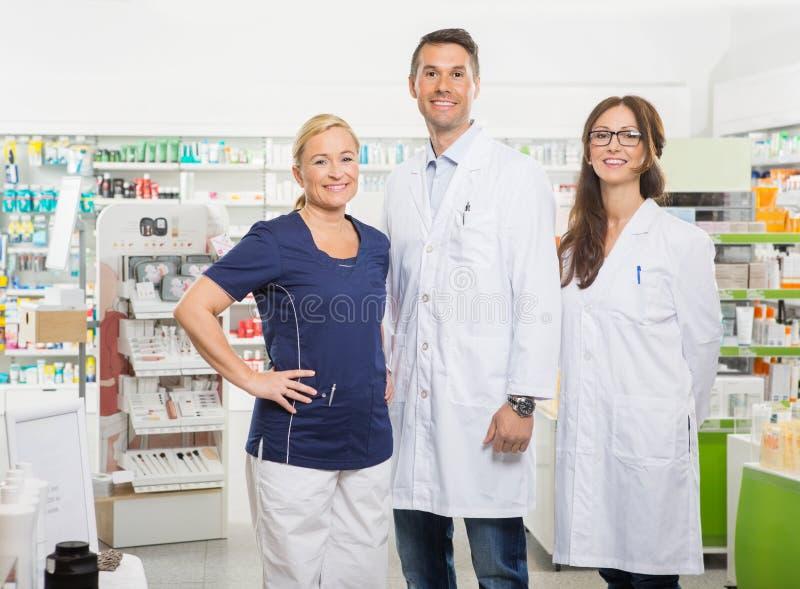 Γυναίκα βοηθός με τους φαρμακοποιούς που στέκονται μέσα στοκ εικόνα με δικαίωμα ελεύθερης χρήσης