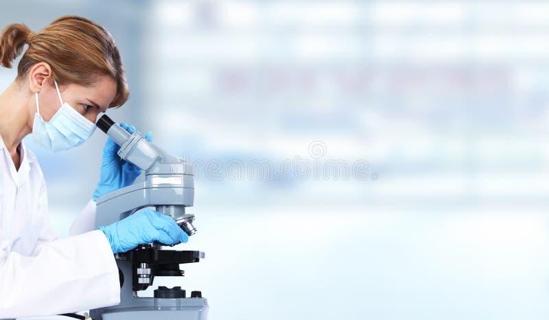 Γυναίκα γιατρών με το μικροσκόπιο στοκ φωτογραφίες