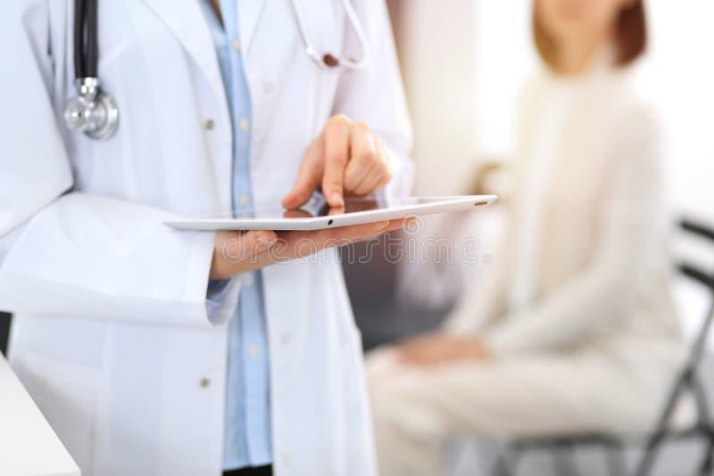 Γυναίκα γιατρών που γεμίζει επάνω την ιατρική μορφή στεμένος κοντά στο γραφείο υποδοχής στην κλινική ή το νοσοκομείο έκτακτης ανά στοκ φωτογραφία με δικαίωμα ελεύθερης χρήσης