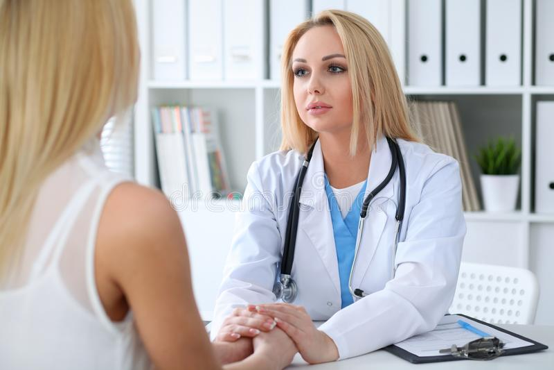 Γυναίκα γιατρών που καθησυχάζει το θηλυκό ασθενή της κρατώντας τα χέρια Έννοια ιατρικής, βοήθειας και υγειονομικής περίθαλψης στοκ εικόνα με δικαίωμα ελεύθερης χρήσης