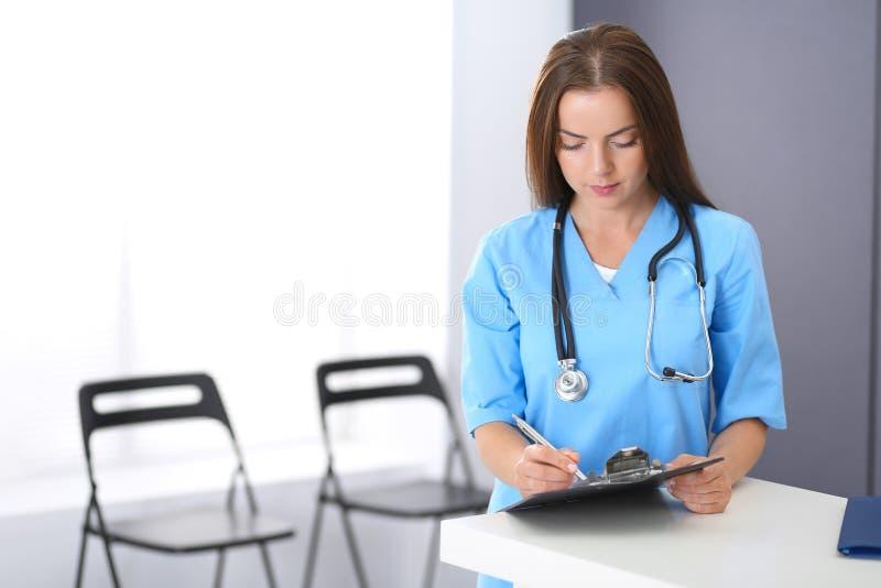 Γυναίκα γιατρών στην εργασία Πορτρέτο του θηλυκού παθολόγου που γεμίζει επάνω την ιατρική μορφή στεμένος κοντά στο γραφείο υποδοχ στοκ φωτογραφίες
