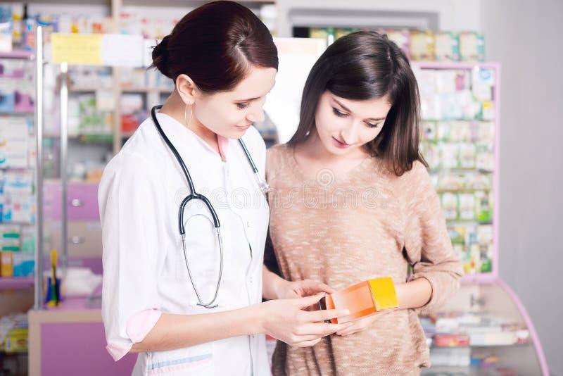 Γυναίκα γιατρών στο ομοιόμορφο παρουσιάζοντας προϊόν στον πελάτη στοκ εικόνα με δικαίωμα ελεύθερης χρήσης