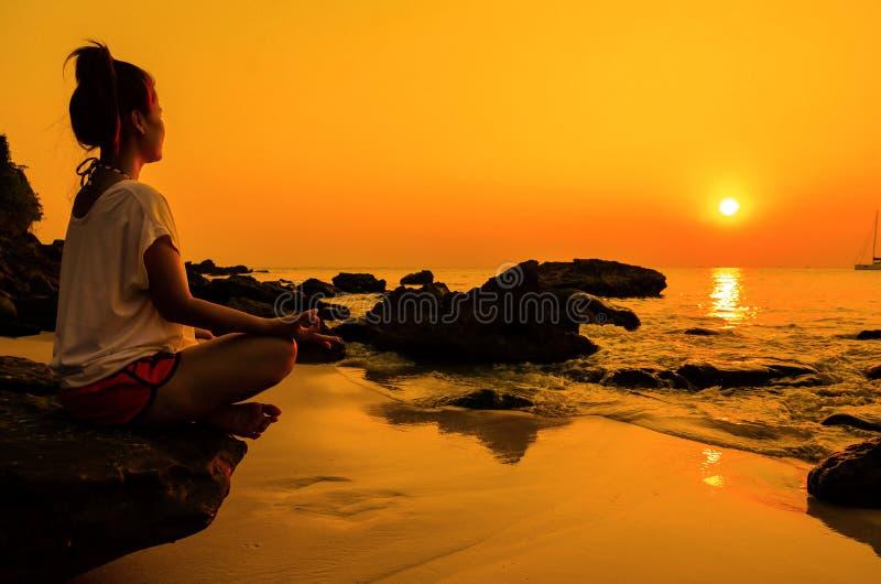 γυναίκα γιόγκας ηλιοβασιλέματος με την πνευματικότητα στην παραλία στοκ φωτογραφία με δικαίωμα ελεύθερης χρήσης
