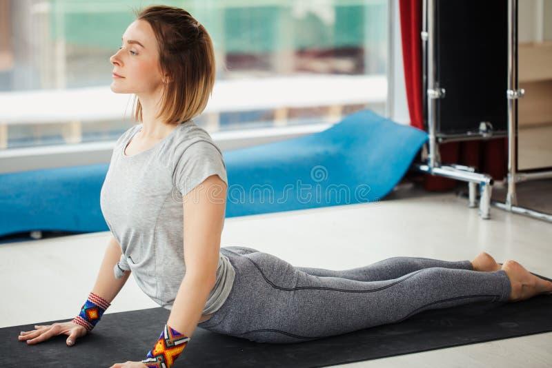 Γυναίκα γιόγκας που κάνει την τεντώνοντας άσκηση στο πάτωμα στοκ εικόνες με δικαίωμα ελεύθερης χρήσης