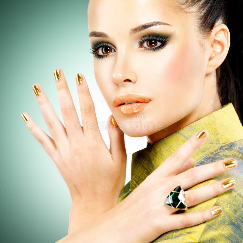 Γυναίκα γοητείας με τα όμορφα χρυσά καρφιά και το σμαραγδένιο δαχτυλίδι στοκ εικόνες