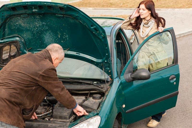 Γυναίκα διακοπής αυτοκινήτων που απαιτεί την οδική βοήθεια στοκ εικόνα
