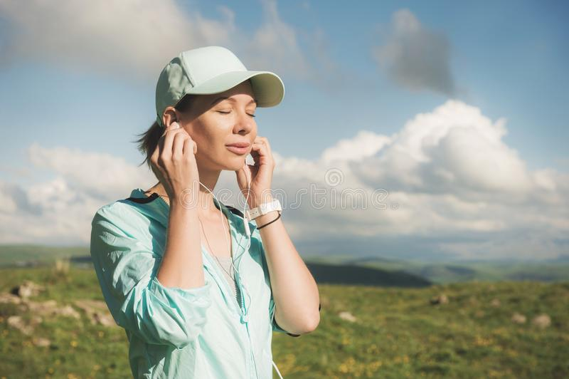 Γυναίκα δρομέων ικανότητας που κλείνει τα μάτια του που ακούνε τη μουσική στη φύση Πορτρέτο του όμορφου κοριτσιού που φορά τα ακο στοκ εικόνες