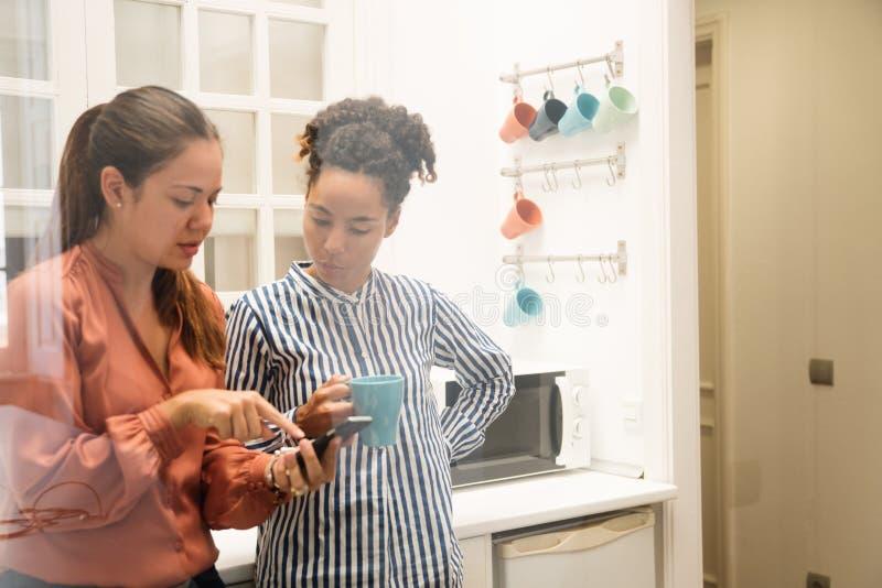 Γυναίκα δύο που μιλά σε μια κουζίνα γραφείων στοκ φωτογραφία
