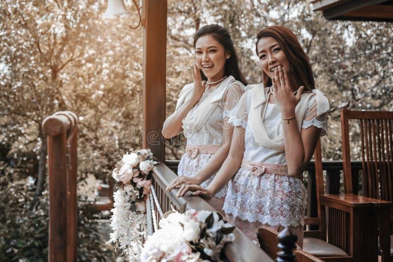 Γυναίκα δύο στο ταϊλανδικό παραδοσιακό φόρεμα στο ξύλινο σπίτι στοκ φωτογραφία