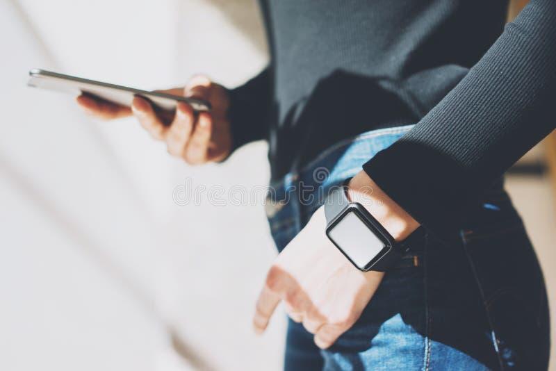 Γυναίκα εικόνων που απασχολείται στο σύγχρονο στούντιο, που φορά το γενικό έξυπνο ρολόι σχεδίου Θηλυκά χέρια σχετικά με το κινητό στοκ εικόνα